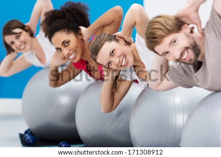 Diverse group of young friends having fun at the gym working out with gym balls doing Pilates exercises to tone their muscles turning to smile at the camera - stock photo