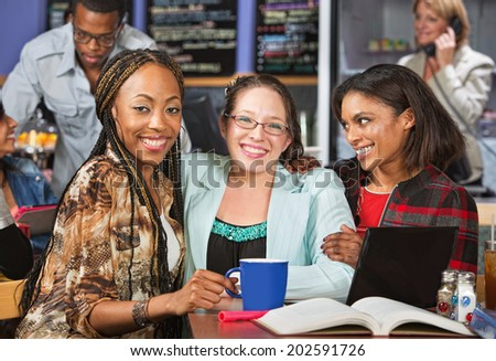 Diverse group of young women studying in cafe