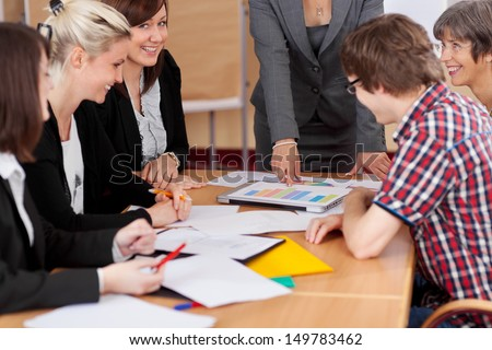 Diverse group pf young business people seated round a table discussing graphs in a business meeting - stock photo