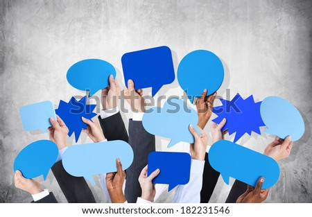 Diverse Hands Holding Blue Speech Bubbles - stock photo