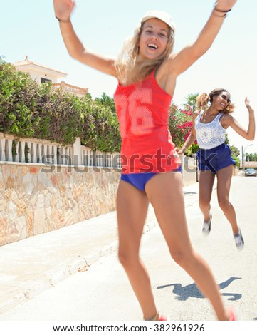 Diverse joyful teenagers girls friends having fun together in a suburban home exterior street jumping up with energy in sunny outdoors. Sporty action living. Adolescents enjoying holiday, smiling. - stock photo