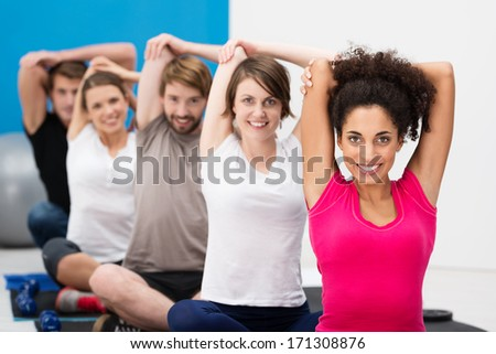 Diverse multiethnic group of fit young friends exercising together in class at the gym sitting cross legged on their mats doing stretching exercises - stock photo