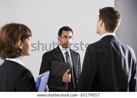 Diverse people in business suits, standing together in serious mood, focus on man wearing eyeglasses - stock photo