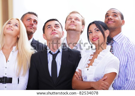 Diverse team of happy business people looking upwards at copyspace - stock photo