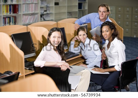 Diverse university students sitting  at library computer studying together - stock photo