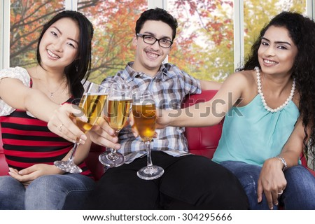 Diversit: people drinking and toasting champagne with autumn background - stock photo