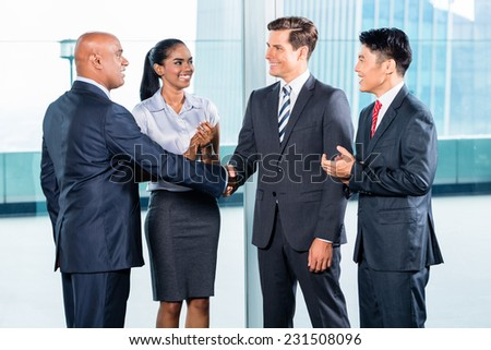 Diversity business team concluding contract with handshake in front of city skyline - stock photo