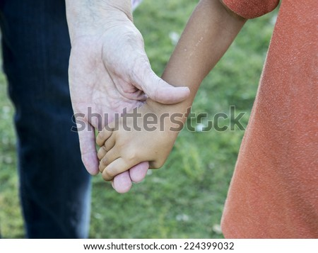 Diversity:  old and young hands. Adoption contest - stock photo