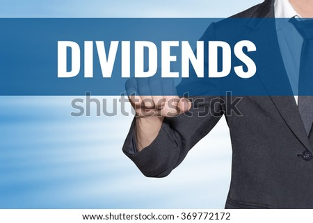 Dividends word Business man touching on blue virtual screen - stock photo