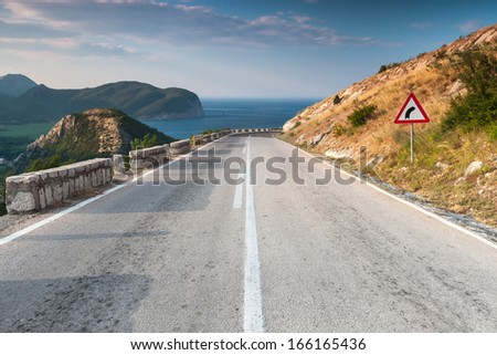 Dividing line and right turn sign on the coastal mountain highway. Montenegro - stock photo