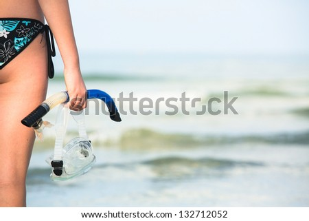 Diving, girl with equipment for snorkeling standing on sand and going to swim in sea (picture with space for text) - stock photo