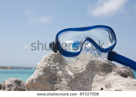 Diving goggles on a rock in front of the sea - stock photo
