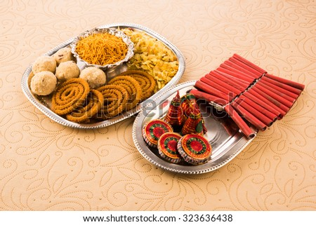 diwali food / snacks /sweets with fire crackers in silver plate isolated over decorative background & Diwali Food Snacks Sweets Fire Crackers Stock Photo (Royalty Free ...