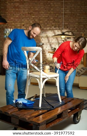 Diy couple renewing chair, painting wooden surface. - stock photo