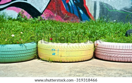 DIY Recycle of tyre used in garden. Flowers and plant in old tire painted pastel color in public park. DIY creative vintage style. Recycled rubber design with folk wisdom. Front view. Close up. - stock photo