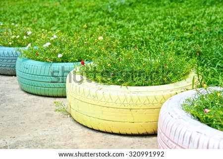 DIY Recycle of tyre used in garden. Flowers and plant in old tire painted pastel color in public park. DIY creative vintage style. Recycled rubber design with folk wisdom. Do it yourself. Close up. - stock photo