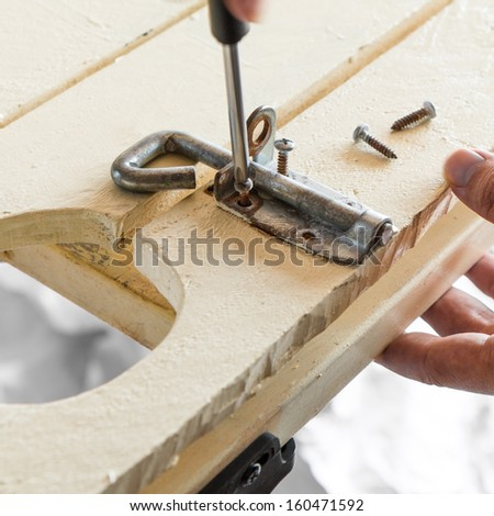 DIY Screwing Bolt Lock.  Square crop of a man unscrewing an old rusty screw from a lock bolt casing. - stock photo