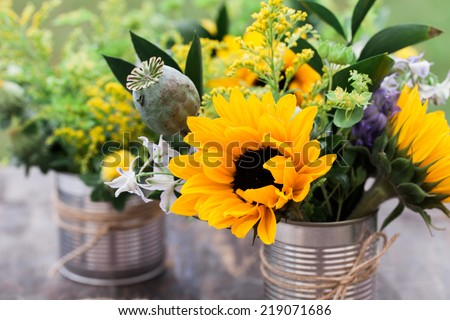 DIY vase with wild flowers on a garden table. - stock photo
