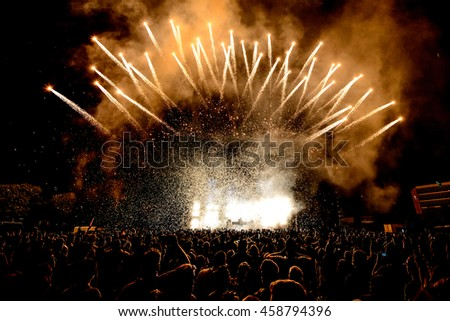 DJ Concert Festival with Special Effects Fireworks over the Silhouette Crowd Backlit