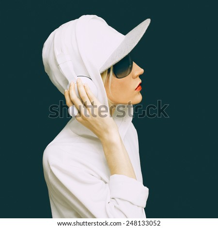 DJ Girl in white clothes sports listening to Music on black background. Urban fashion style - stock photo