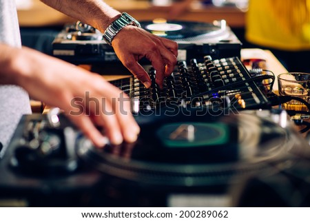 DJ hands on equipment - stock photo