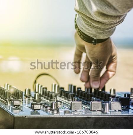 Dj hands on equipment deck and mixer - stock photo