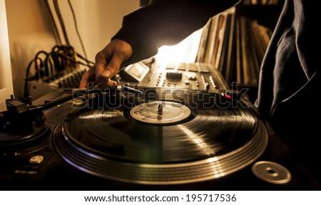 Dj in studio puts needle on record  - stock photo
