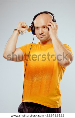 DJ man with headphones and handcuffs on his hand - stock photo