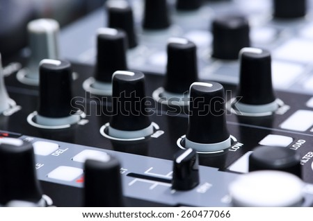 DJ mixer controller - fader and buttons of cool silver vinyl mixing console in nightclub; selective focus - stock photo