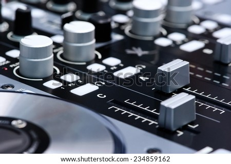 DJ mixer controller. Faders and switches of silver audio mixing console in nightclub. Selective focus. - stock photo