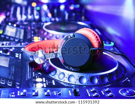Dj mixer with headphones at nightclub - stock photo