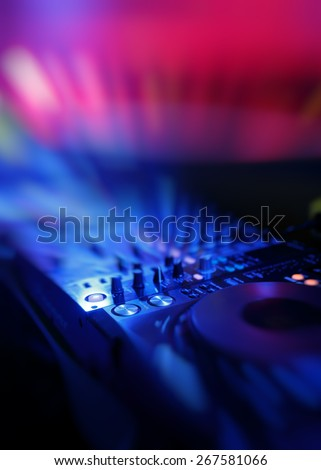 DJ mixer with light colored spotlights discos, shallow depth of field and beautiful swirling bokeh - stock photo