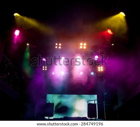 DJ mixes place on scene at nightclub. Bright beautiful lighting - stock photo