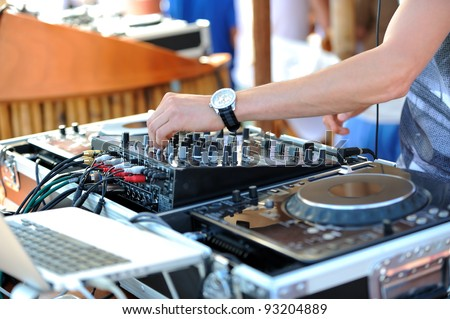 Dj mixes the track in the beach bar - stock photo