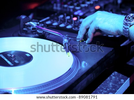 Dj mixes the track in the nightclub at a party. Vinyl Player in the foreground