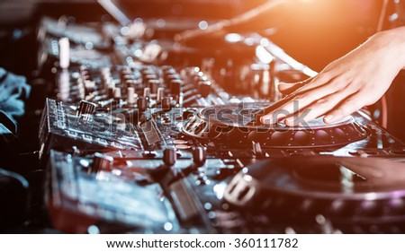 Dj mixes the track in the nightclub at party, close-up. - stock photo