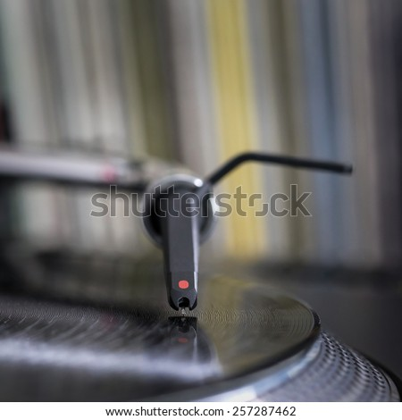 Dj needle stylus on spinning record, vinyl background 