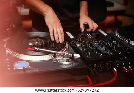 Dj play music at hip hop party.Turntable vinyl record player,analog sound technology for disc jockey to scratch vinyl records and mix tracks.DJ scratching record,cut with cross fader regulator knob