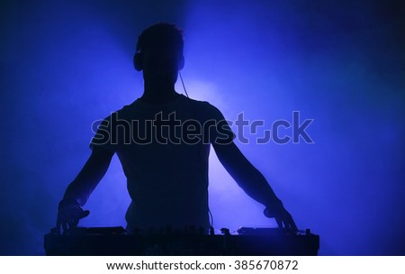 DJ playing music at mixer on color foggy background - stock photo