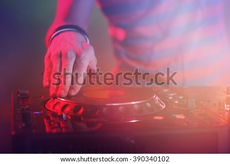 DJ playing music at mixer on colorful blurred background - stock photo