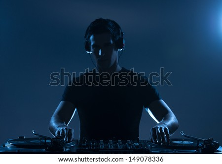 DJ playing music. Confident young DJ spinning on turntable while standing isolated - stock photo