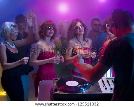 dj playing music with vinyl records, turntables and headphones in front of young attractive dancing crowd with sunglasses, surounded by colorful lights