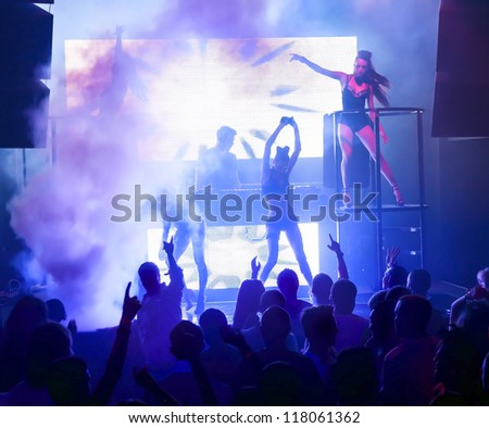 Dj playing on stage in smoke. Silhouettes female dancers and people in motion, dancing at nightclub - stock photo