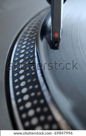 DJ record player with a macro closeup of the stylus on a 12 inch vinyl LP playing hiphop techno rave beats. - stock photo