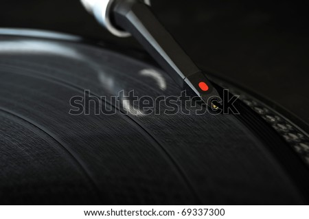 DJ record turntable. Macro closeup of the needle on a 12 inch vinyl LP playing hiphop techno rave beats. - stock photo