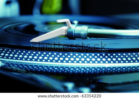Dj turntable vinyl record player playing disc with music. Analog audio equipment for disc jockey, party in nightclub or concert. Close up, focus on turntables needle and head shell