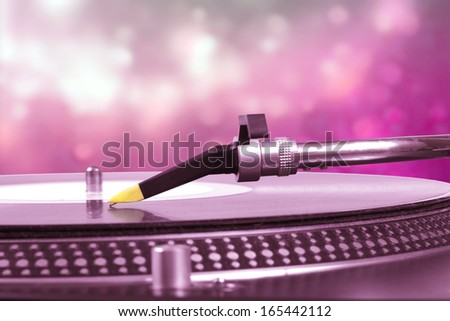 dj turntable with pink bokeh background - stock photo
