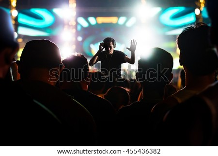 DJ with headphones at concert under ray of illuminated and crowd people - stock photo