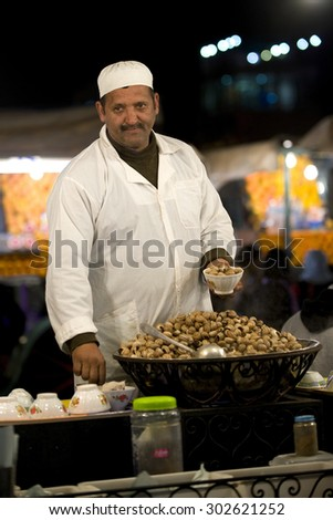 DJEMMA AL FNA, MARRAKESH, MOROCCO - JULY 2010: Snail food stall seller in Djemaa Al Fna in Marrkesh  - stock photo