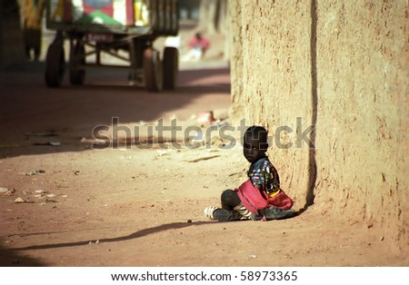 DJENNE, MALI - JANUARY 16: A Fulani child sits in the dust on the unpaved road on January 16, 2006, Djenne, Mali. Children in Mali are starving and have no hope for the future. - stock photo